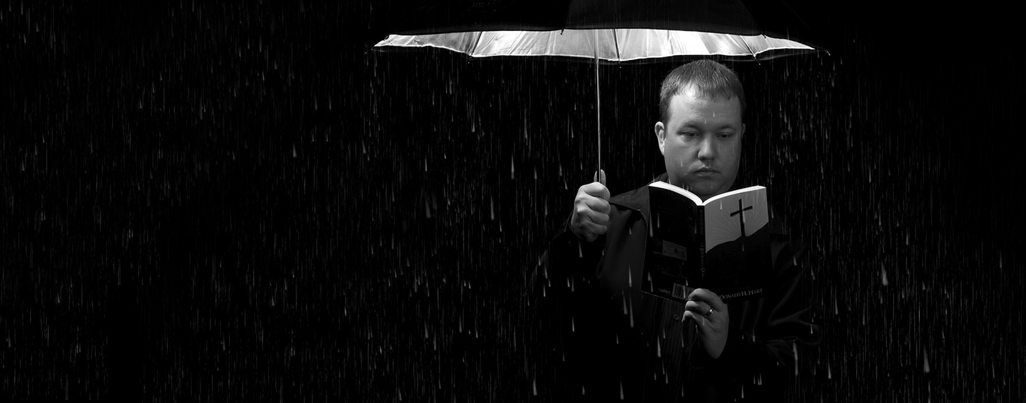 Man stood in the rain reading