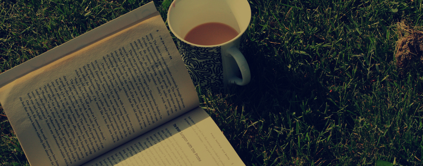 A book and cup of tea out on the grass